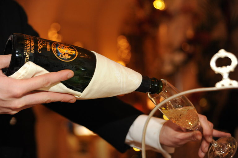 Miss Windsor's Delectables - Christmas Afternoon Tea at The Ritz, London. Waiter pours a glass of - Reserve Ritz Champagne Barons De Rothschild